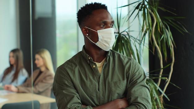 Молодой афро-американский мужчина в медицинской маске смотрит в камеру в современном офисе бизнесмена в офисе на карантине из-за пандемии коронавируса