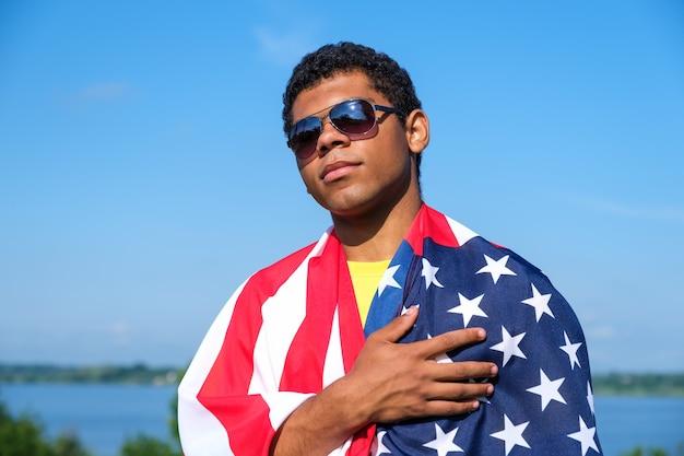 선글라스를 쓴 젊은 아프리카계 미국인 남자는 자랑스럽게 어깨에 미국 국기를 들고 푸른 하늘을 배경으로 심장에 손을 얹습니다