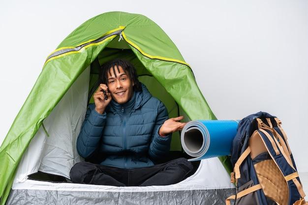 Молодой афроамериканец человек в зеленой палатке кемпинга, ведение разговора с кем-то мобильного телефона