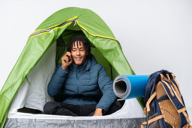 Молодой афроамериканец человек в зеленой палатке кемпинга, ведение разговора с мобильного телефона