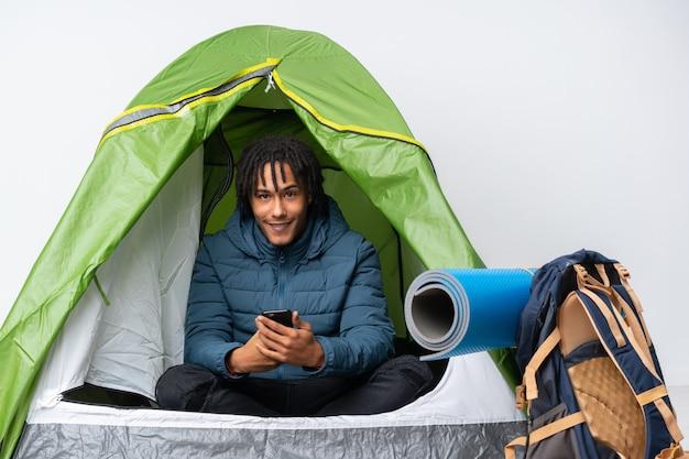 Молодой афроамериканец человек в зеленой палатке, отправив сообщение с мобильного телефона