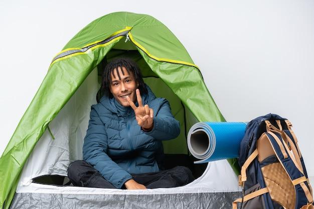 笑みを浮かべて勝利のサインを示すキャンプの緑のテントの中の若いアフリカ系アメリカ人