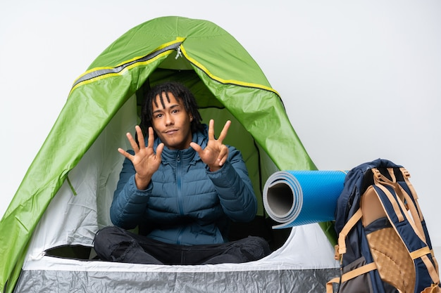Young african american man inside a camping green tent counting eight with fingers