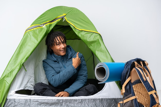 Young african american man inside a camping green tent pointing back