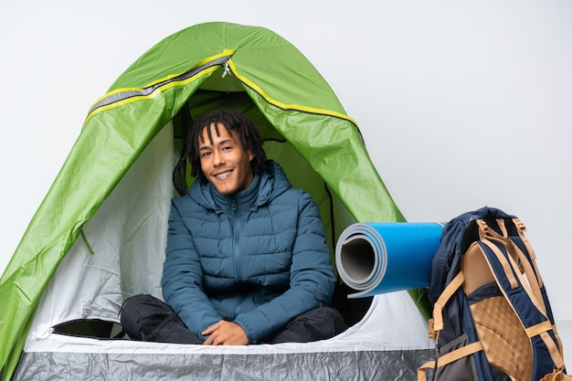Young african american man inside a camping green tent with arms crossed and looking forward