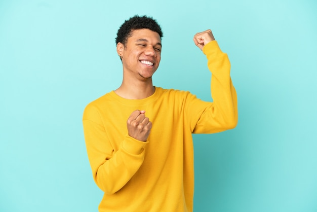 Young african american man isolated on blue background celebrating a victory