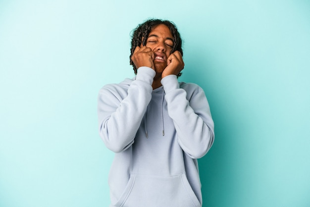 Young african american man isolated on blue background crying, unhappy with something, agony and confusion concept.