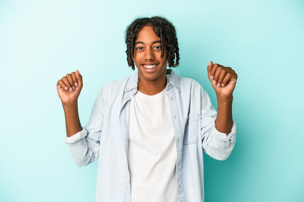 Young african american man isolated on blue background dancing and having fun.
