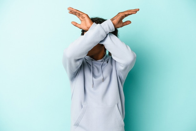 Young african american man isolated on blue background keeping two arms crossed, denial concept.