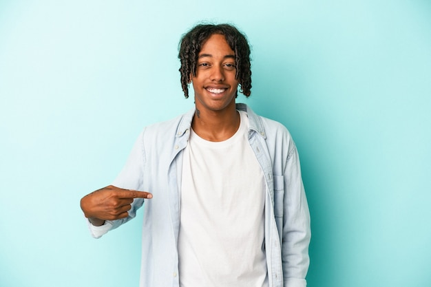 Young african american man isolated on blue background person pointing by hand to a shirt copy space, proud and confident