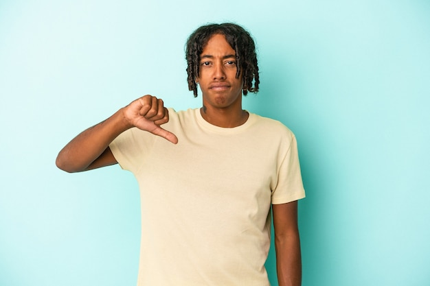 Young african american man isolated on blue background showing thumb down, disappointment concept.