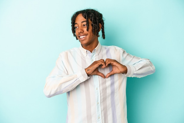 Young african american man isolated on blue background smiling and showing a heart shape with hands.