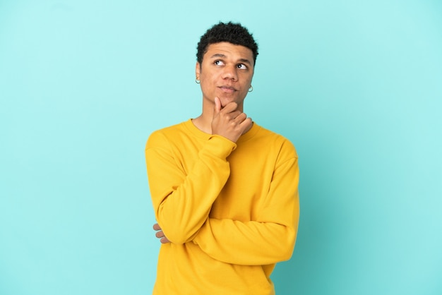Young african american man isolated on blue background thinking an idea while looking up