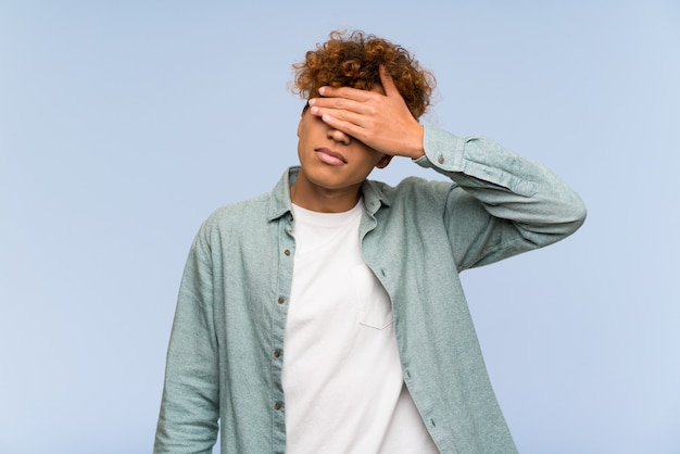 Young african american man over isolated blue wall covering eyes by hands. do not want to see something