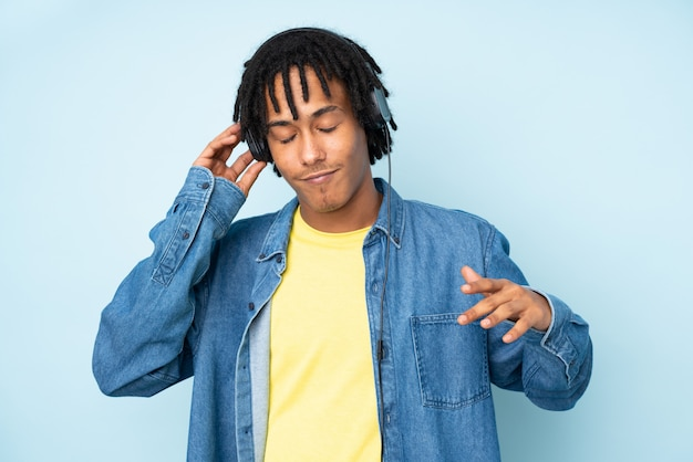 Young african american man isolated on blue wall listening music and dancing