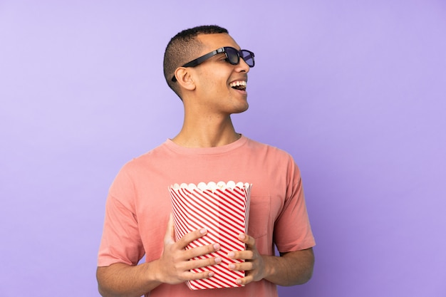 Young african american man over isolated blue wall with 3d glasses and holding a big bucket of popcorns