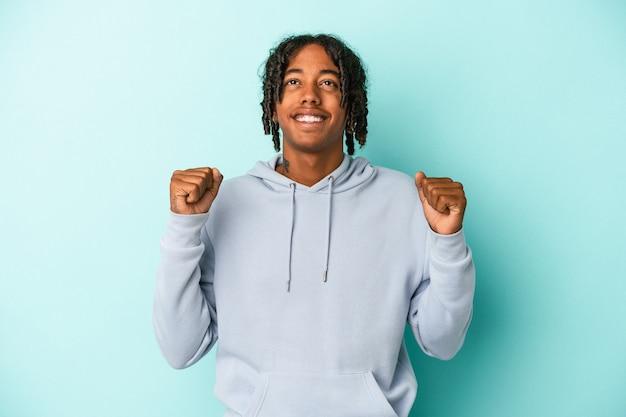 勝利、情熱と熱意、幸せな表現を祝う青い背景に孤立した若いアフリカ系アメリカ人の男。