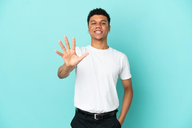 Молодой афроамериканец, изолированные на синем фоне, считая пять пальцами