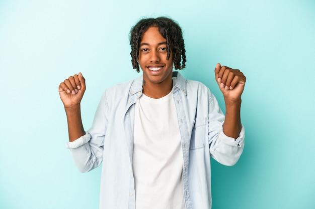 파란색 배경에 고립된 젊은 아프리카계 미국인 남자가 춤을 추고 즐거운 시간을 보내고 있습니다.