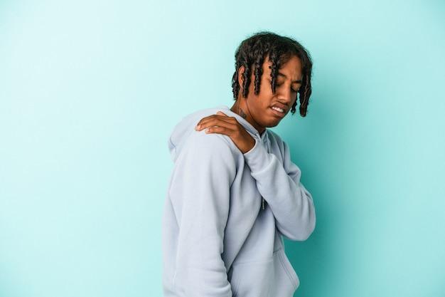 肩の痛みを持っている青い背景で隔離の若いアフリカ系アメリカ人の男。