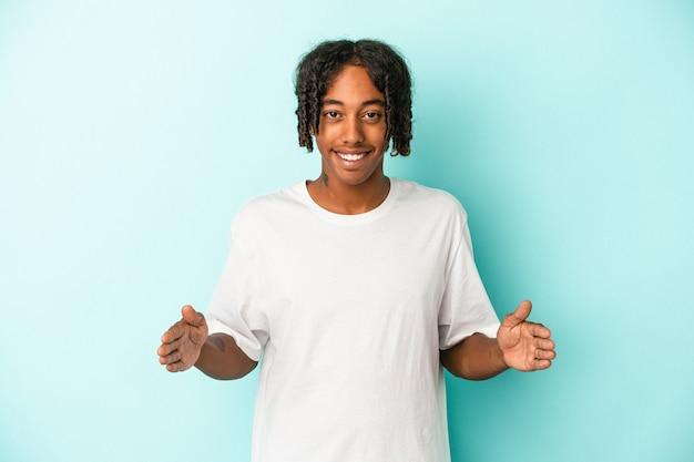 両手で何か、製品のプレゼンテーションを保持している青い背景で隔離の若いアフリカ系アメリカ人の男。