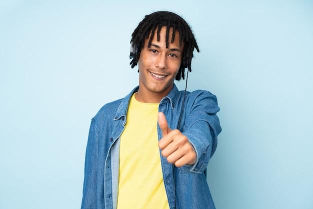 Молодой афроамериканец человек, изолированные на синем фоне прослушивания музыки и с пальца вверх