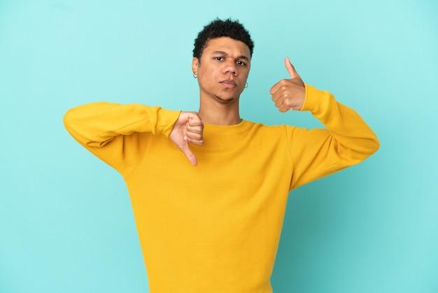 파란색 배경에 격리된 젊은 아프리카계 미국인 남자가 좋은-나쁜 기호를 만듭니다. 예, 아니요 미정