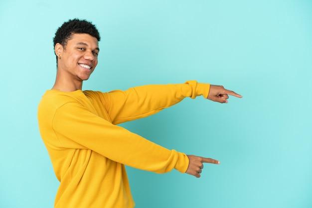 Молодой афро-американский мужчина изолирован на синем фоне, указывая пальцем в сторону и представляет продукт