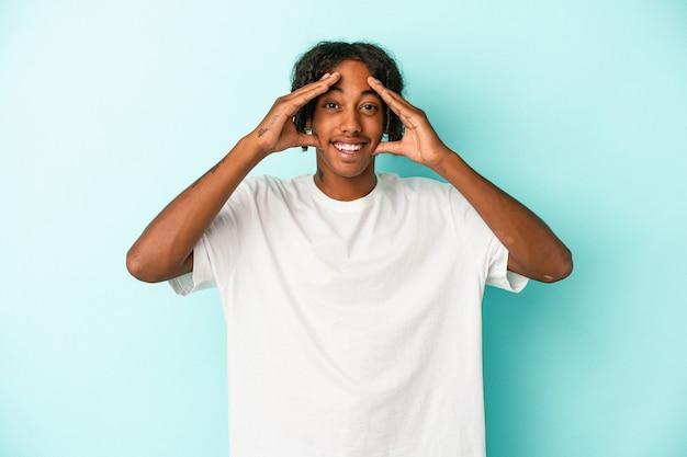 青い背景に孤立した若いアフリカ系アメリカ人の男は、嬉しい驚きを受け取り、興奮し、手を上げます。