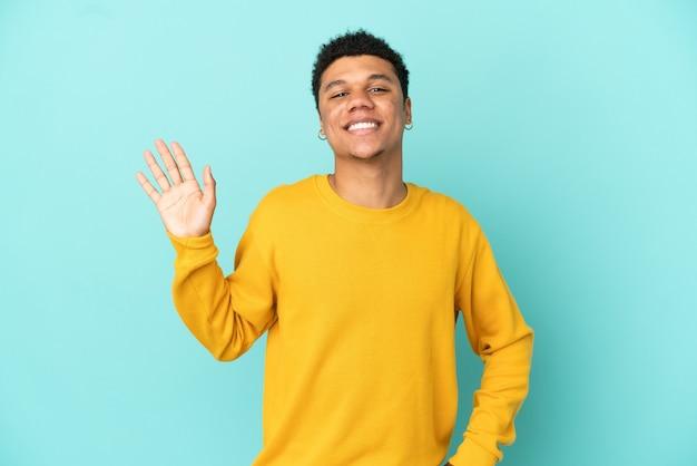 Молодой афро-американский мужчина изолирован на синем фоне, салютуя рукой с счастливым выражением лица
