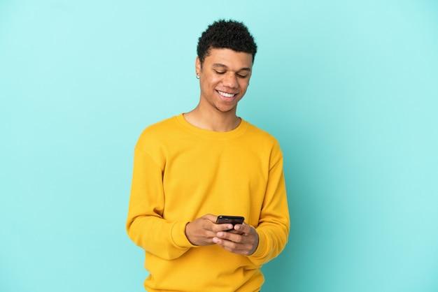 Молодой афро-американский мужчина изолирован на синем фоне, отправляя сообщение с мобильного телефона