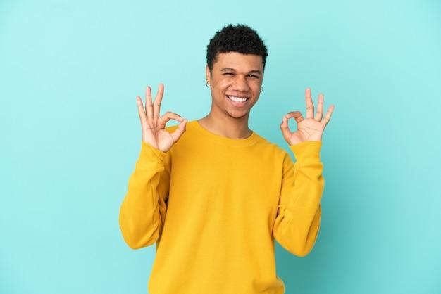 Молодой афроамериканец, изолированные на синем фоне, показывает знак ок двумя руками