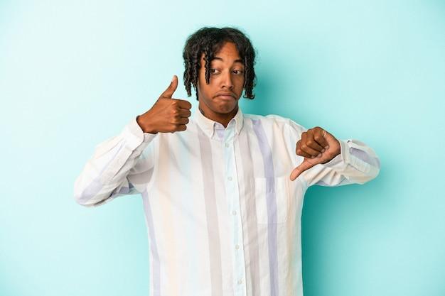 親指を上と親指を下に示す青い背景に分離された若いアフリカ系アメリカ人の男、難しい選択の概念