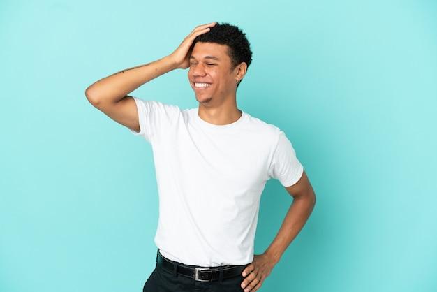 Молодой афро-американский мужчина, изолированные на синем фоне, много улыбаясь