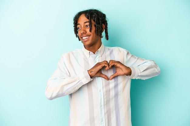 笑顔と手でハートの形を示す青い背景で隔離の若いアフリカ系アメリカ人の男。
