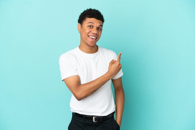 Молодой афро-американский мужчина, изолированные на синем фоне, удивлен и указывает сторону