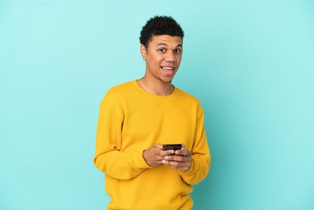 Молодой афроамериканец, изолированный на синем фоне, удивился и отправил сообщение