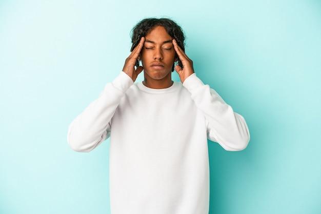 파란색 배경에 고립된 젊은 아프리카계 미국인 남자는 사원을 만지고 두통을 앓고 있습니다.
