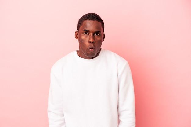ピンクの背景に孤立した若いアフリカ系アメリカ人の男は、頬を吹く、疲れた表情をしています。表情のコンセプト。