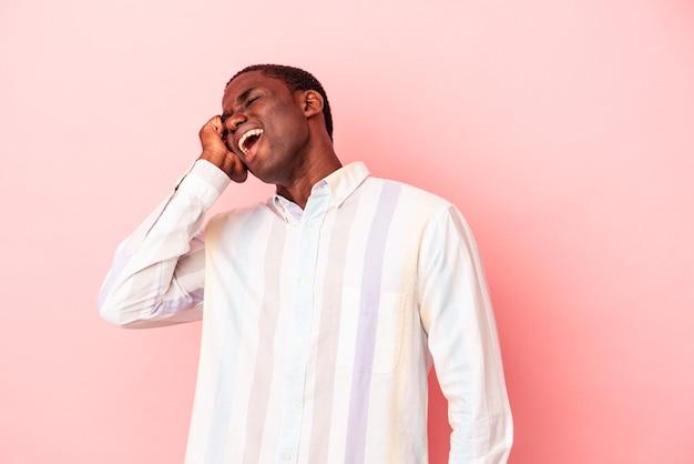 勝利、情熱と熱意、幸せな表現を祝うピンクの背景に孤立した若いアフリカ系アメリカ人の男。