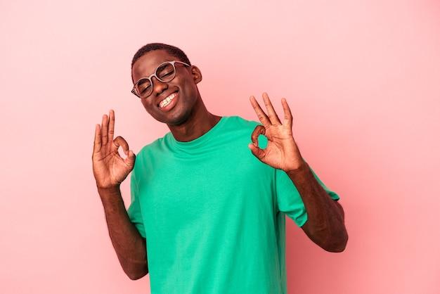 ピンクの背景に孤立した若いアフリカ系アメリカ人の男は、陽気で自信を持って大丈夫なジェスチャーを示しています。
