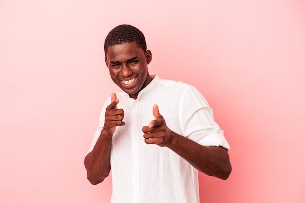 ピンクの背景に孤立した若いアフリカ系アメリカ人の男性は、正面を指している陽気な笑顔。
