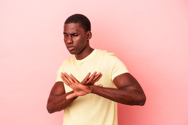 拒否ジェスチャーをしているピンクの背景に分離された若いアフリカ系アメリカ人の男