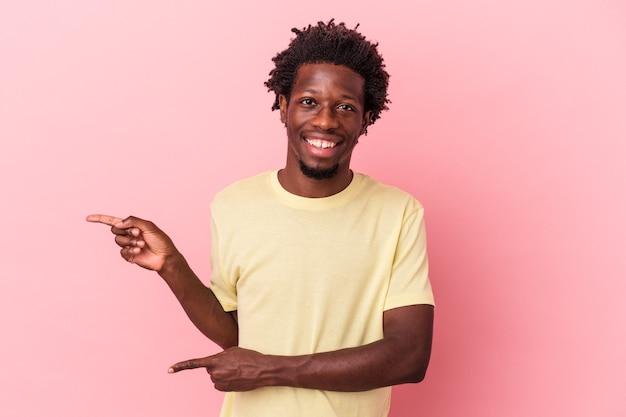 ピンクの背景に孤立した若いアフリカ系アメリカ人の男は、人差し指を離れて指して興奮しました。