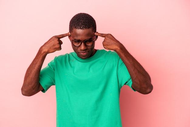 ピンクの背景に孤立した若いアフリカ系アメリカ人の男は、人差し指を頭に向けたまま、タスクに焦点を当てました。