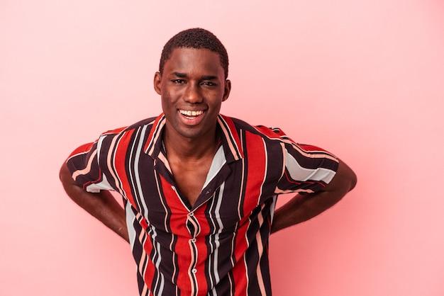 ピンクの背景に孤立した若いアフリカ系アメリカ人の男は幸せ、笑顔、陽気な。