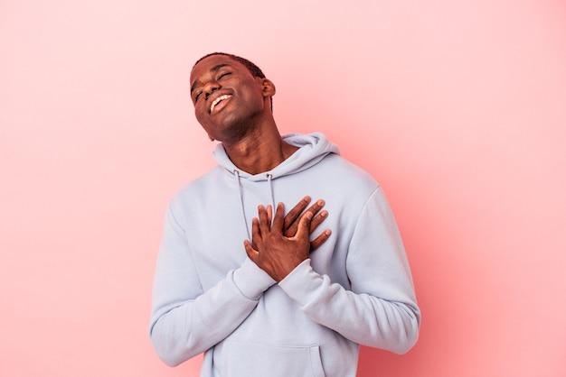 ピンクの背景に分離された若いアフリカ系アメリカ人の男性は、手のひらを胸に押して、フレンドリーな表情をしています。愛の概念。