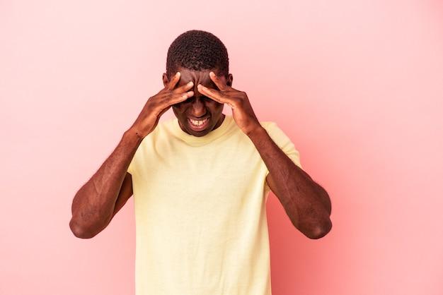 顔の正面に触れて、頭痛を持っているピンクの背景に孤立した若いアフリカ系アメリカ人の男。