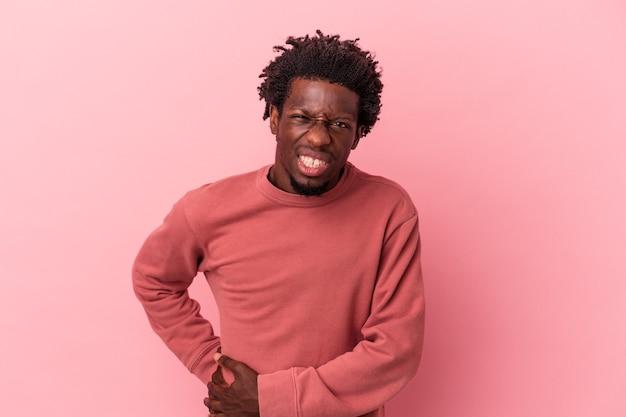 肝臓の痛み、胃の痛みを持っているピンクの背景に分離された若いアフリカ系アメリカ人の男。
