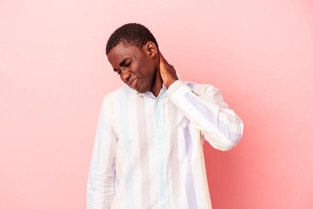 ピンクの背景に孤立した若いアフリカ系アメリカ人男性は、ストレス、マッサージ、手でそれに触れることによる首の痛みを持っています。